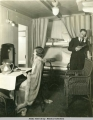 Stateroom scene, woman sitting in front of mirror, man is on phone.