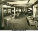View aboard steamship of lounge with chairs and piano.