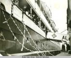 Looking up at passengers on deck, as steamship is preparing for departure.
