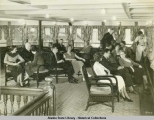 Passengers visiting and relaxing in social hall aboard steamship.