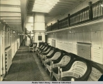 Interior view of social hall aboard steamship.