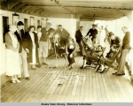 Passengers playing game of shuffleboard on deck of steamship.