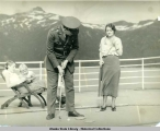 Man and woman playing golf on deck of steamship, mountains in the background.