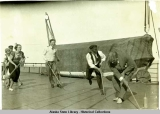Passengers playing game of hockey on top deck of steamship.