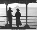 Man and woman standing against rail aboard steamship with island in the background.