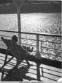 Woman sitting in chair on deck of steamship.