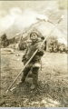 Eskimo boy dressed in fur and holding harpoon.