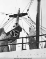 Two men raising Alaska Line flag on steamship.