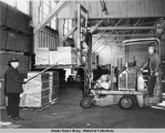 Two men in warehouse stacking boxes with forklift.