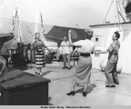 Two men and two women play badminton on deck of S.S. Aleutian.