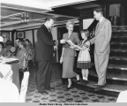 Crewman greets man, woman, and child in dining room, S.S. Aleutian.