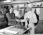 Woman shakes hand of chef in galley aboard steamship.