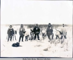Five Eskimo men with reindeer, standing in snow.