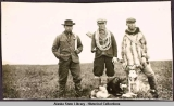 Three Eskimo men standing with several dogs.