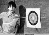 Archery. A young man poses next to three arrows in a target.