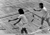 Badminton. Two player with raquets, one prepares to serve.