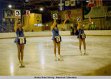 Figure skating. Three ice skaters stand on the ice, holding cards with numbers on them.