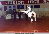 Judo. One man in a match in midst of bringing another to the floor.