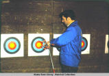 Archery. A man examines locations of arrows in a target.
