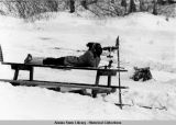 Ski biathlon. A participant lies on a picnic table to look through spotting scope.