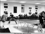 Table tennis. Players on all sides of table play a table tennis match. A row of spectators sit...
