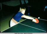 Table tennis. Player leans over table to hit ball.
