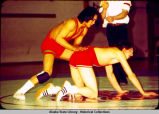 Wrestling. A wrestler stands behind opponent on hands and knees.