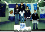 Curling. Four young women stand at winners' podium with regional flags behind them, and curling...