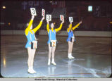 Figure skating. Three young women in skates stand on ice holding cards with numbers on them.