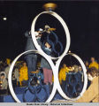 Opening ceremony. Spectators in coats watch as two people stand on podium to light lantern on...