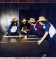 Dance at roller rink. Four young people in straw cowboy hats crowd around shuffle board table.