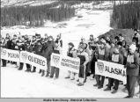 Snowshoeing. Clusters of young people in team coats stand in snow behind banners: Yukon, Quebec,...