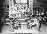 Opening ceremony. Four people in elaborate costumes perform in front of stage.