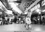 Arrival/Entertainment. A performer in traditional dress holds and wears and holds a number of...