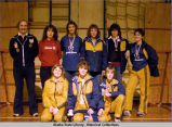 Indoor soccer. A team pose proudly, wearing metals around their necks. Three sit on gym floor and...