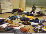 Indoor soccer. A classroom cluttered with sleeping bags, sleep pads, cots, luggage, and debris. A...