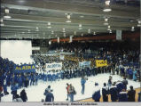 Opening ceremony. Large groups of people in blue uniforms stand on ice rink holding banners:...