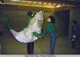 1996 mascot with 1996 Host Society members. Woman and fish mascot shake hands.