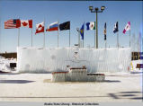 Flags of participating countries, territories, and states fly above ice horseshoe. Winners' podium...