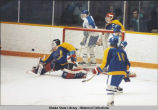 Hockey. The puck sails toward goal. Goalie leans toward it with left knee on ice, right leg...