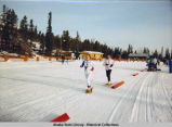 Snowshoeing. Two runners in snowshoes run course. They wear numbers 4 and 9. Spectators and...
