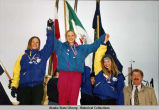 Award ceremonies (sport unknown). Three young women in blue coats and metals stand on winners'...