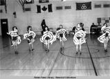 Cultural dance activities. Six women in can-can outfits dance on gym floor.