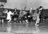 Cultural dance activities. Seven people in Tlingit dress perform on gym floor. One man in a carved...