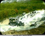 Chevrolet (automobile) crossing glacier stream on highway near Worthington Glacier, below falls.