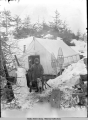 Man and dogs standing outside of tent with snowshoes leaning against it.
