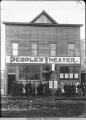 Group of men stand on boardwalk in front of People's Theater. Skagway.