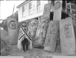 Man in native costume with Chilkat blanket standing by four Shark House posts and four Moon House...