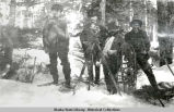 Four men with survey equipment and snowshoes.