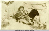 Eskimo woman in parka nursing baby in front of tent.